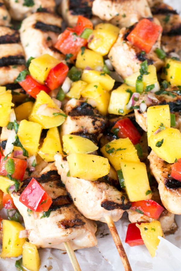 Square overhead image of mango chicken skewers