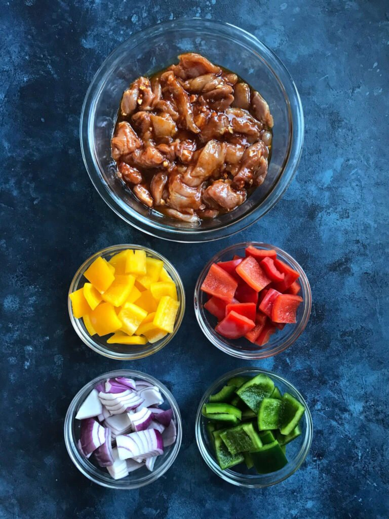 Ingredients for BBQ chicken Skewers - marinated chicken, yellow, red, and green bell pepper and red onions
