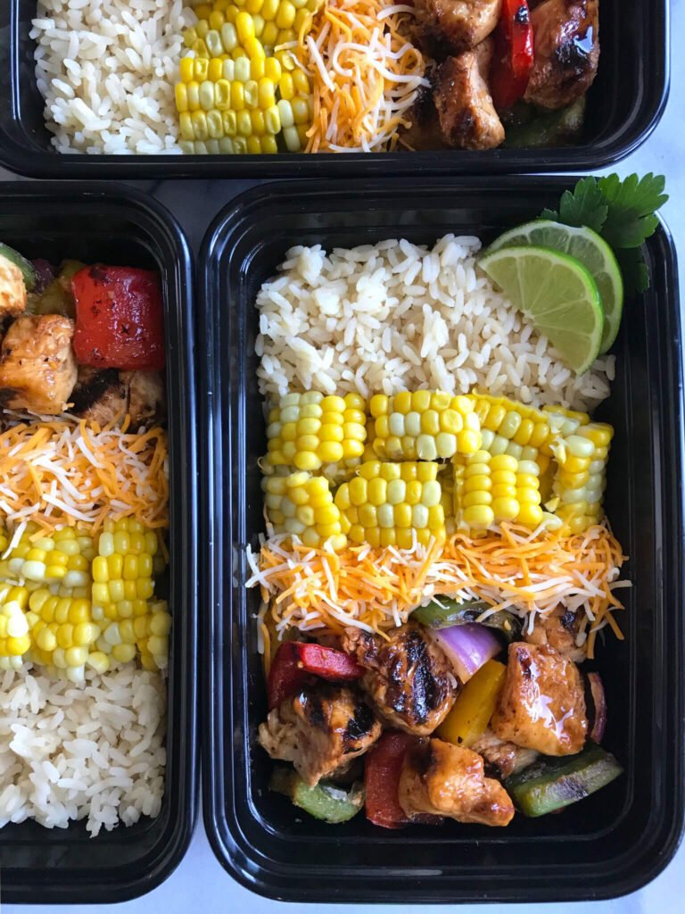 Boxes of meal-prepped lunches: Rice, fresh corn, cheese, and chicken shish kabobs