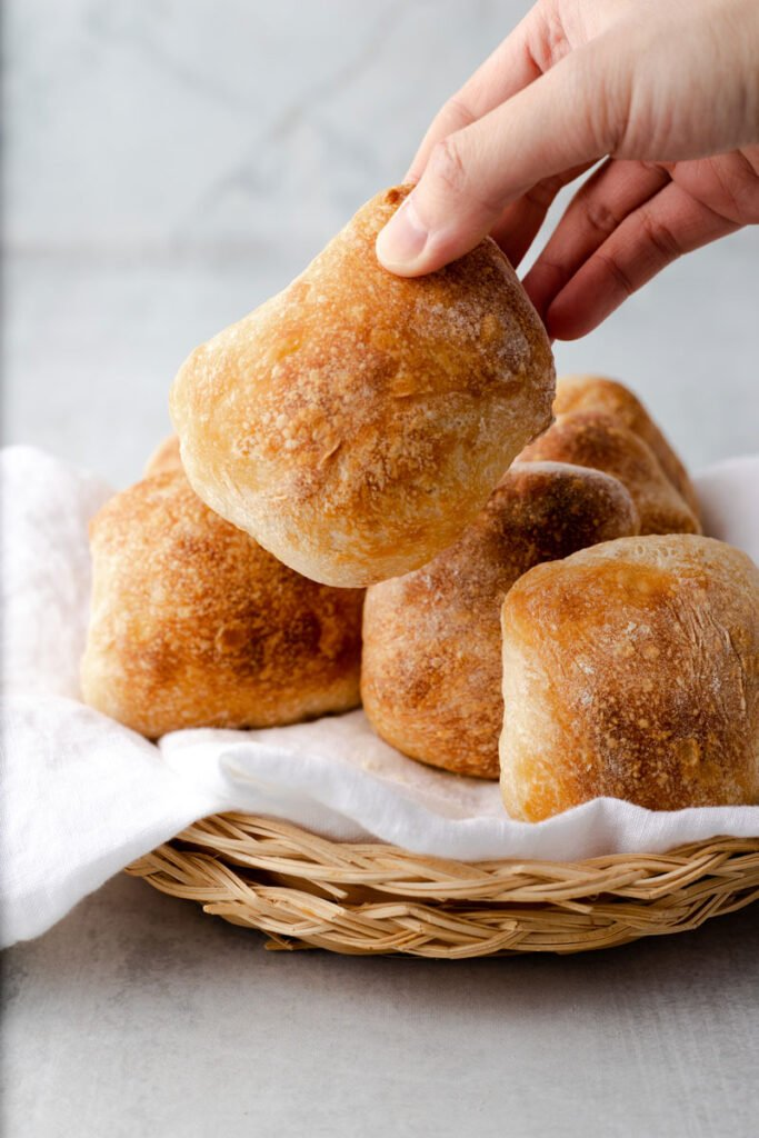 Hand lifting up a ciabatta bread roll.
