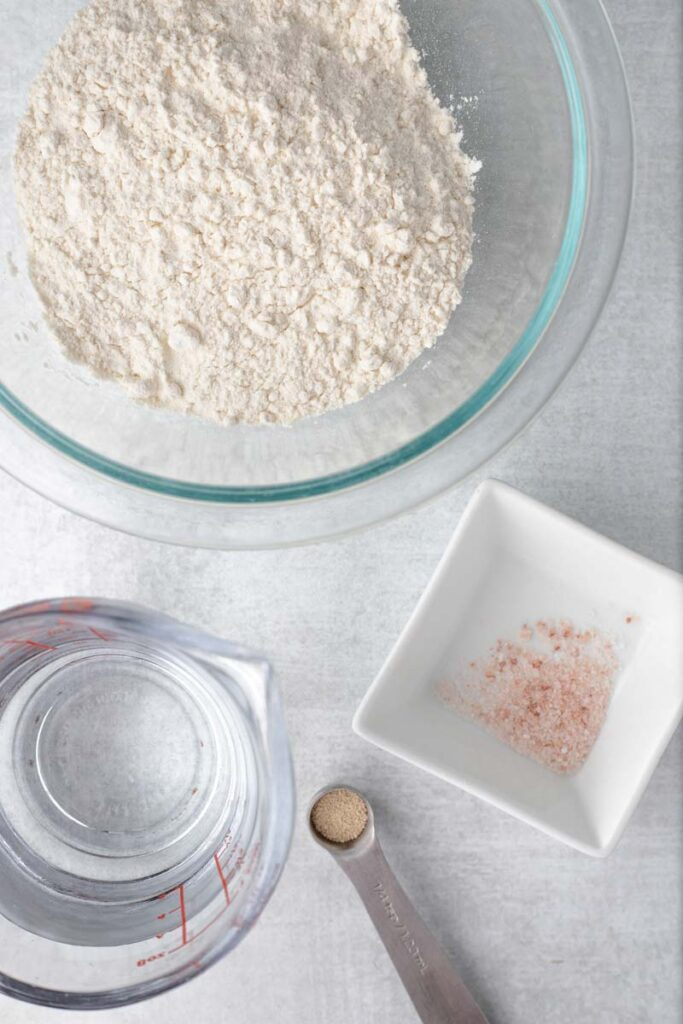 Overhead view of flour, water, yeast, and salt.
