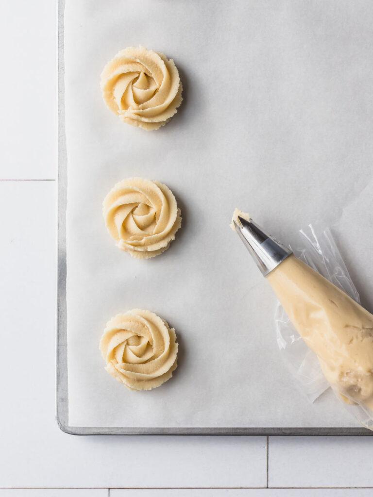 Piping dough on a baking sheet.