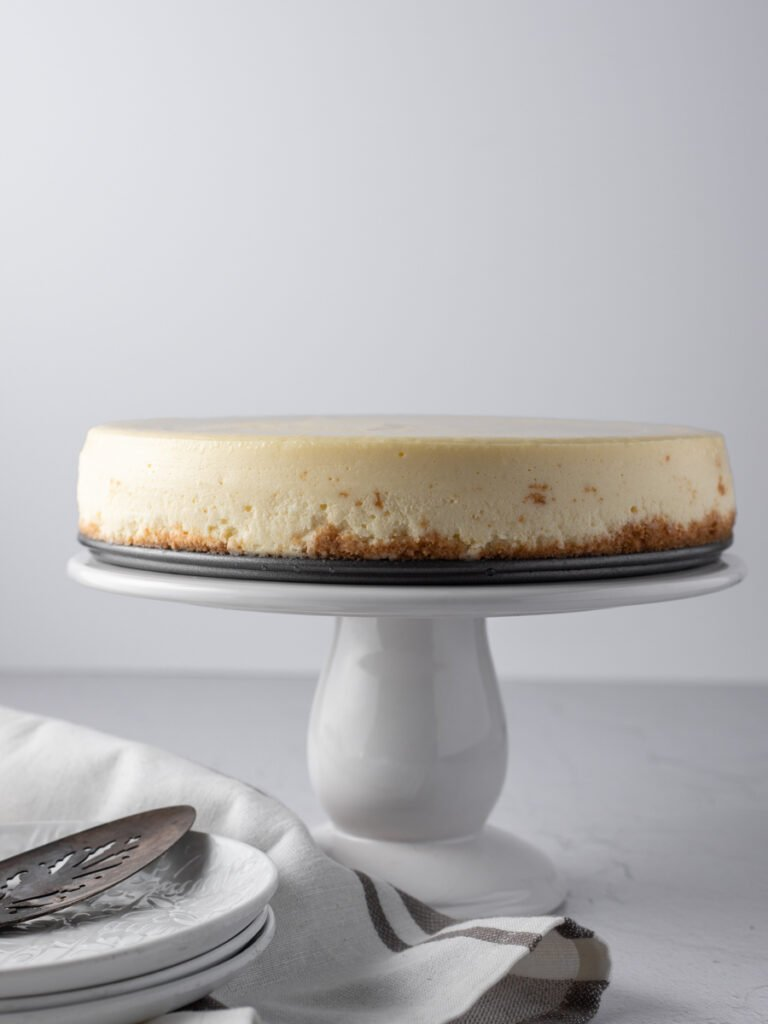 A whole New York cheesecake on a white cake stand.