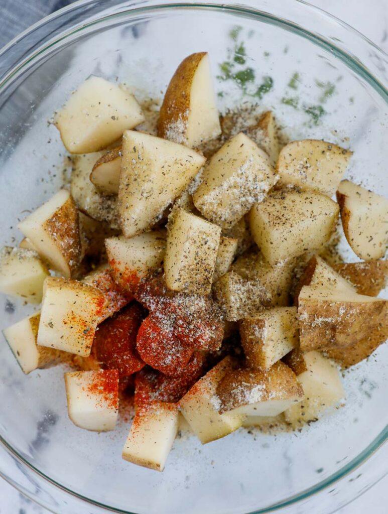 Seasoning cut up potatoes before air frying.