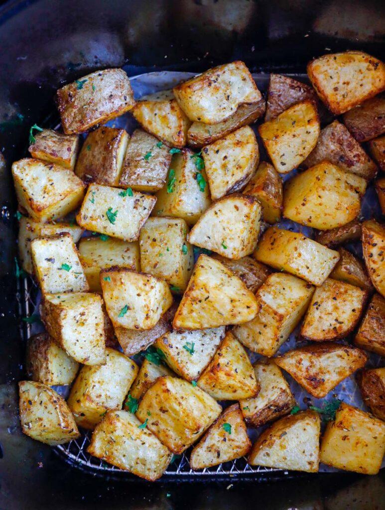 Potatoes inside of an air fryer basket.