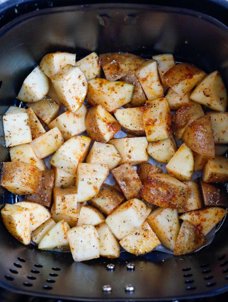Potatoes in an air fryer basket before cooking.