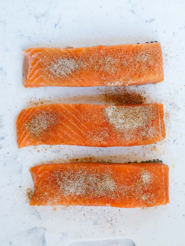 Top down shot of salmon fillets with seasoning.