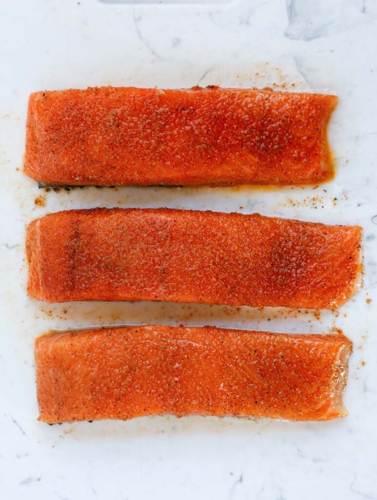 Overhead shot of three raw salmon fillets with seasoning.