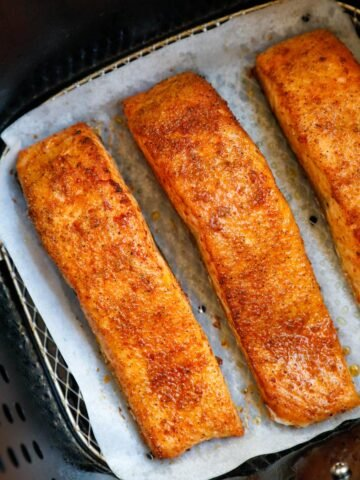 Cooked salmon fillets in an air fryer.