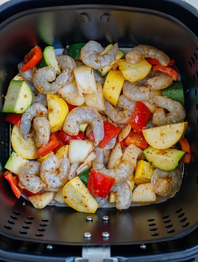Raw shrimp and vegetables in an air fryer.