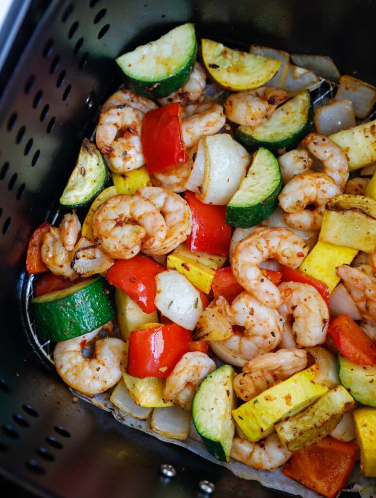 Cooked shrimp and vegetables in an air fryer.