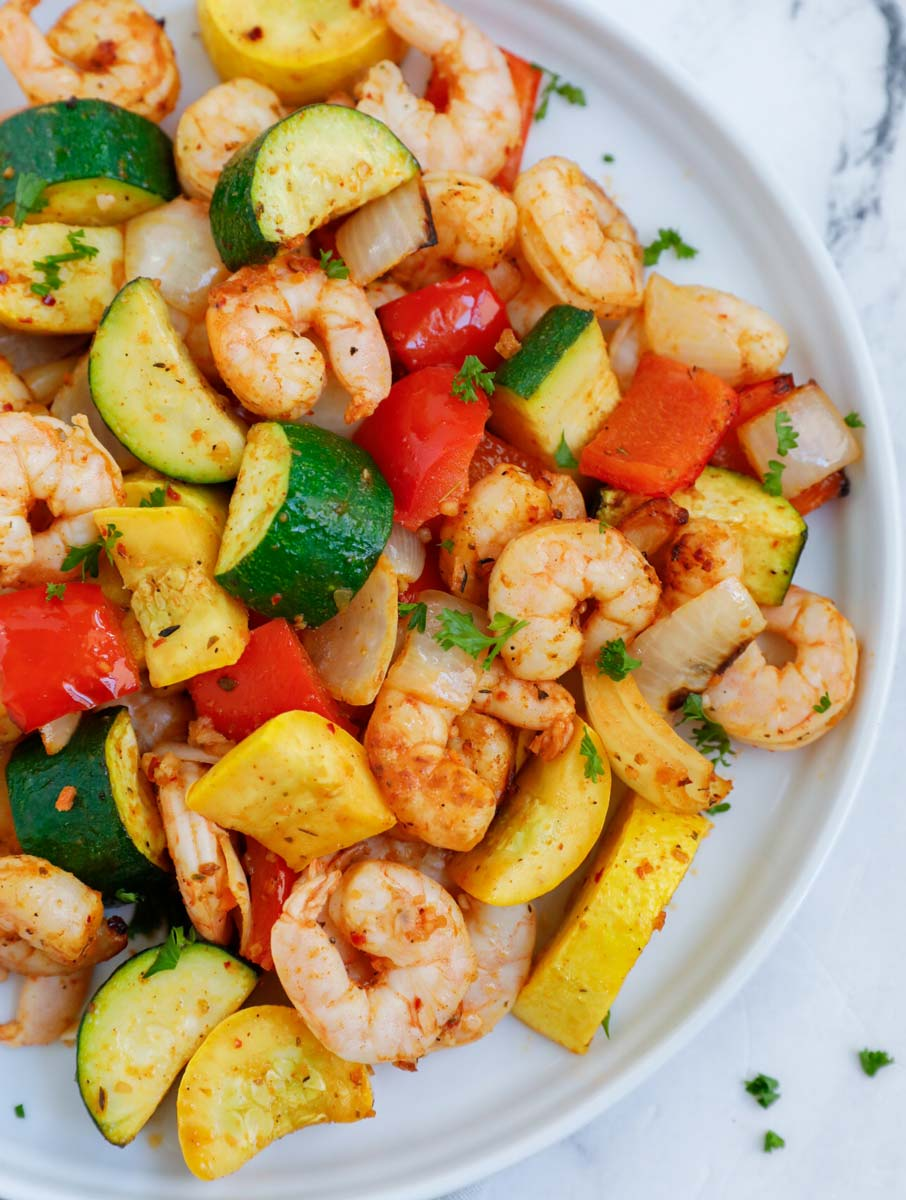 Top down shot of air fryer shrimp and vegetables on a plate.