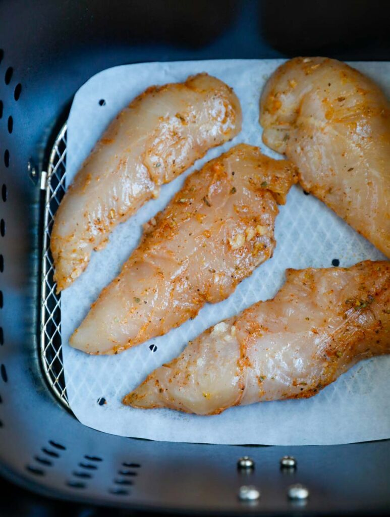 Raw chicken in an air fryer.
