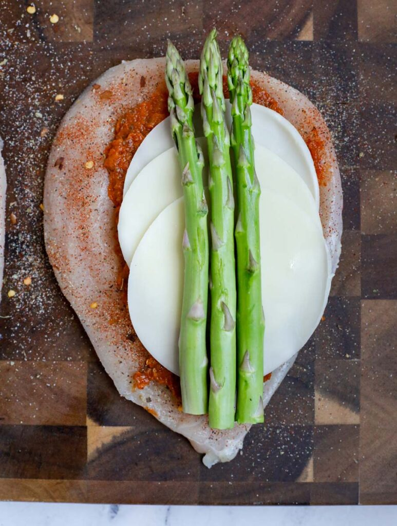 Chicken breast with pesto, cheese and asparagus.