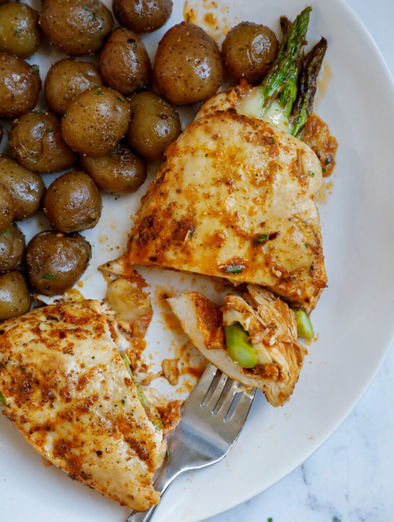 Top down shot of asparagus stuffed chicken with potatoes on the side.