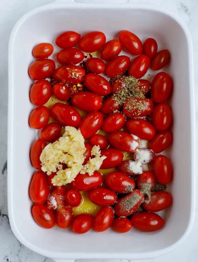 Tomatoes in a baking dish with seasoning.