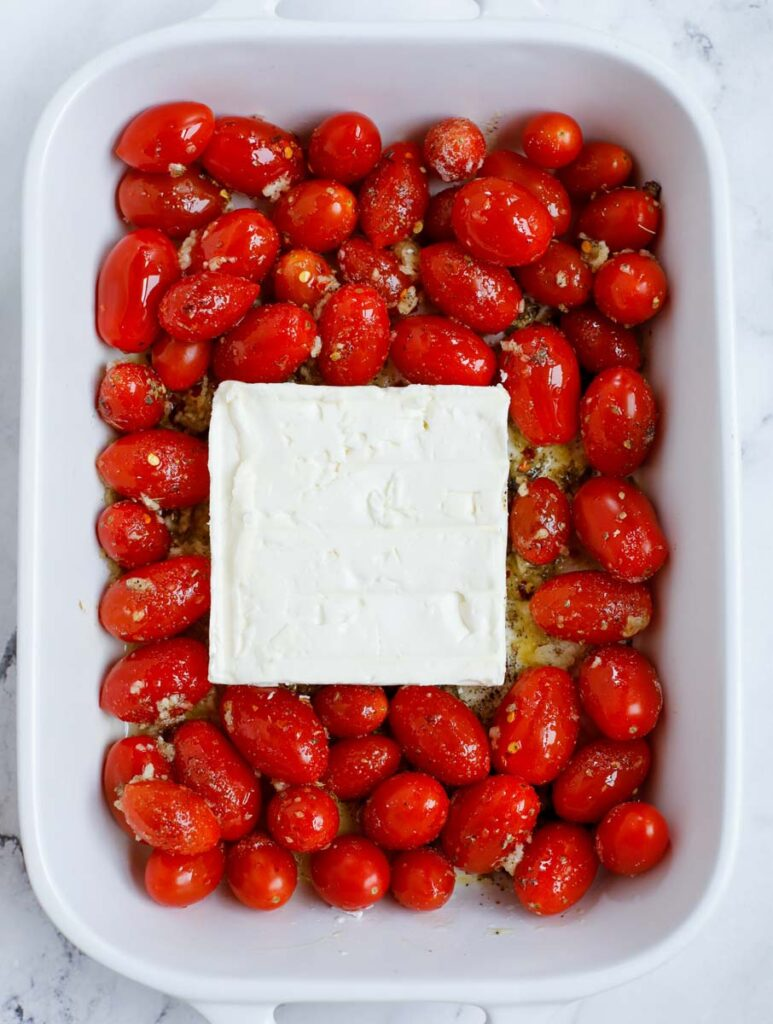 A block of feta in a dish with tomatoes.