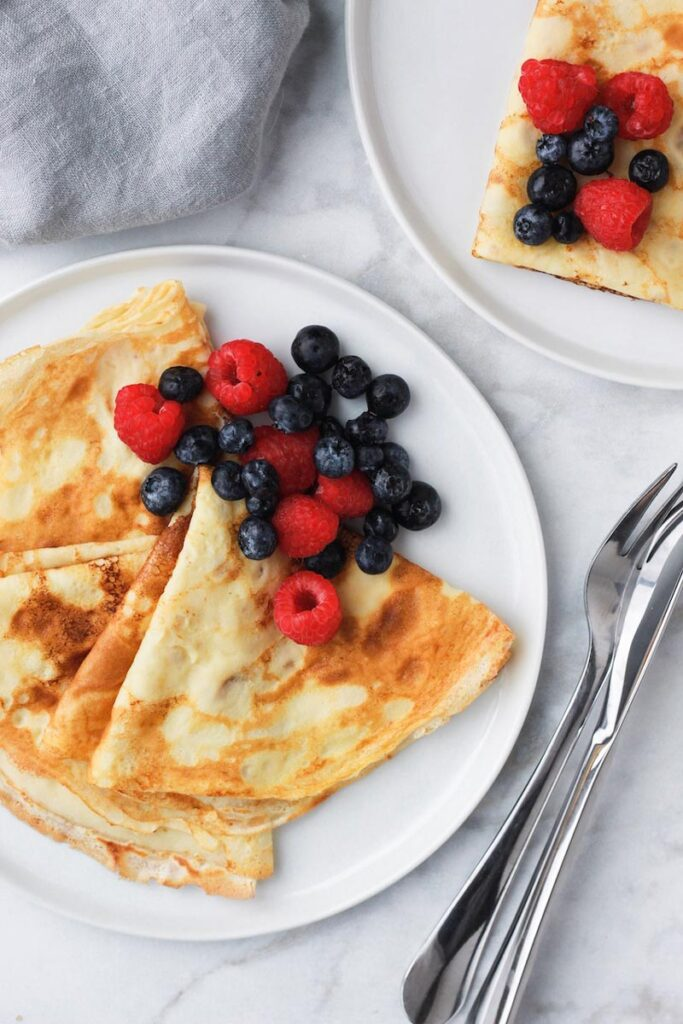 Crepes on a plate with berries.