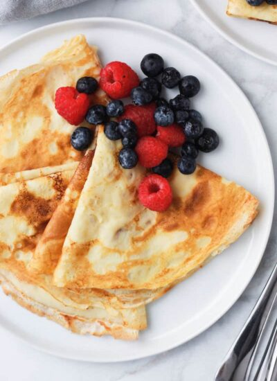 crepes and berries served on a plate