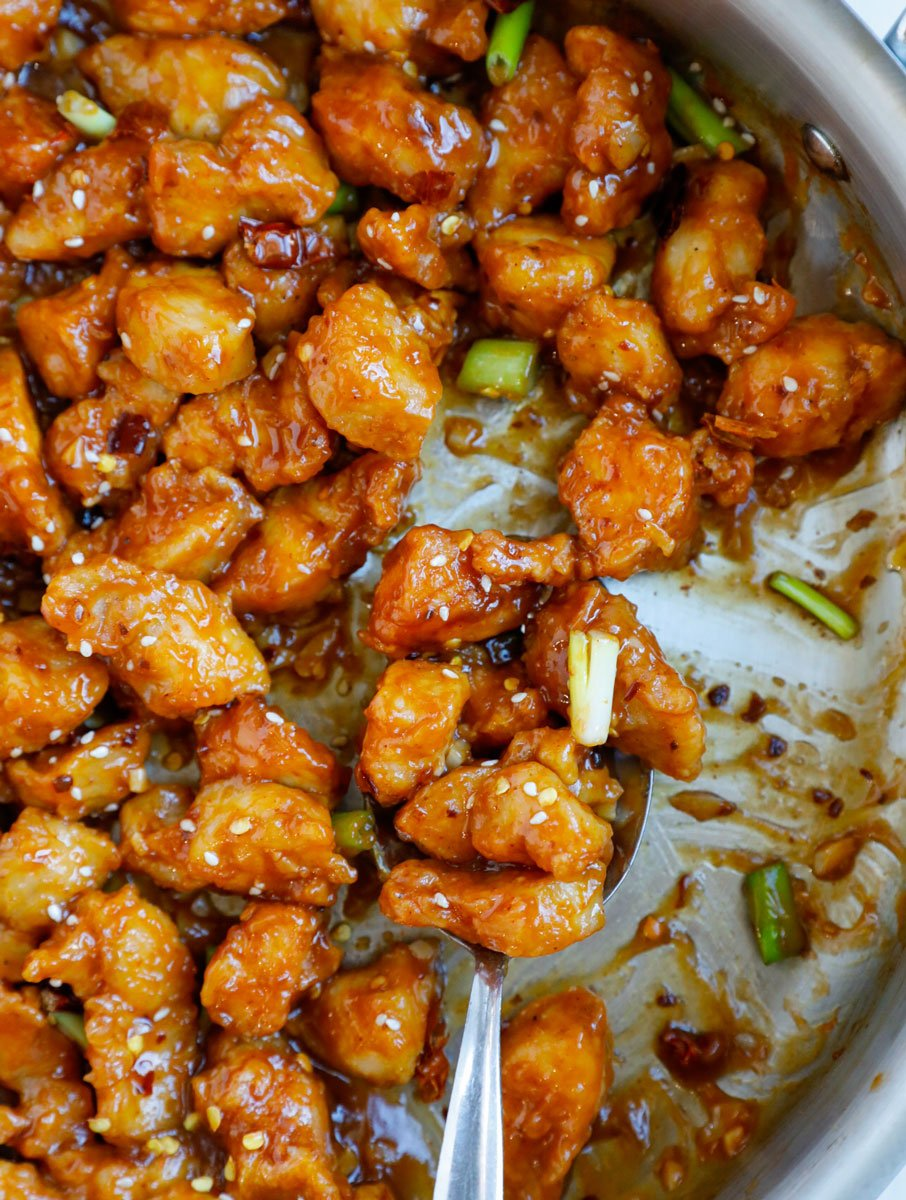 Close up of a spoonful of crispy general tso chicken.
