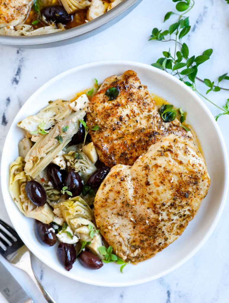 greek chicken breasts served on a white plate
