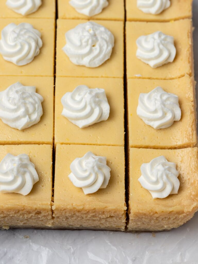 lemon bars cut out and topped with whipping cream