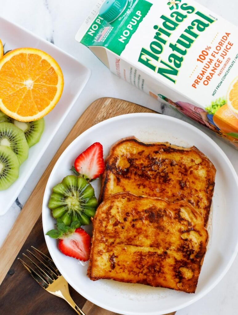 A plate of french toast made with orange juice.