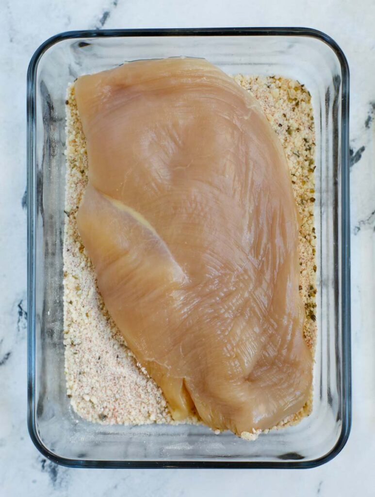 Chicken breast added to a container to be coated by flour and seasoning.