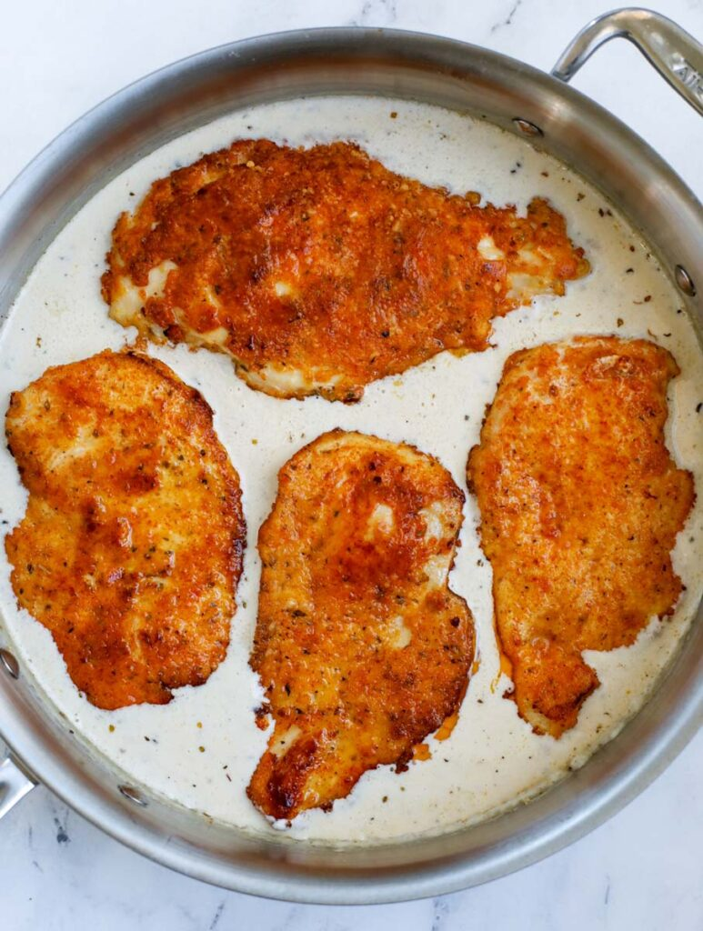 Adding crispy chicken to a skillet of sauce.