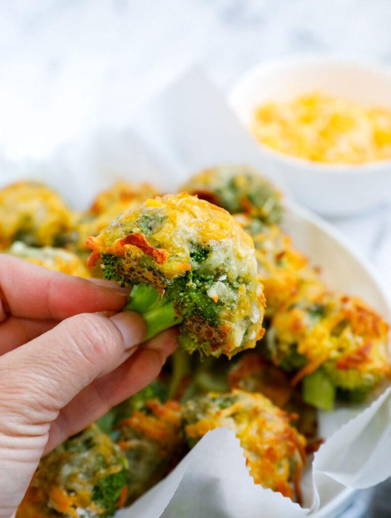Hand holding a cheesy broccoli bite.