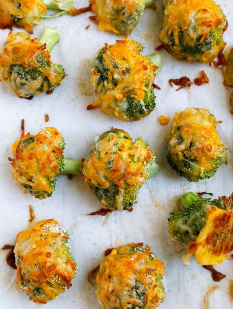 Cheesy broccoli bites on a baking sheet.