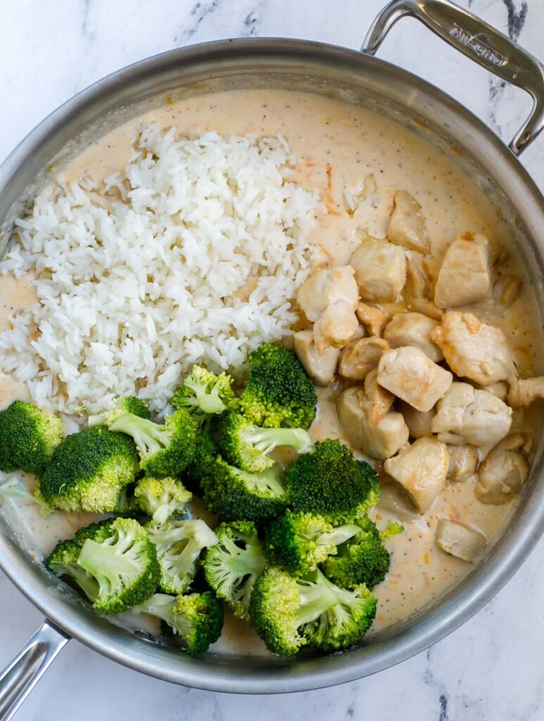 A silver skillet with a smooth creamy casserole sauce on the bottom and cooked rice, chicken, and broccoli on the top.