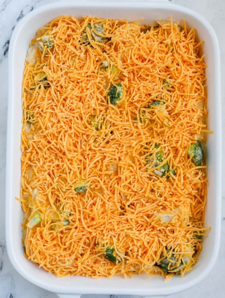 A white casserole dish with chicken broccoli rice casserole with cheddar cheese before baking.