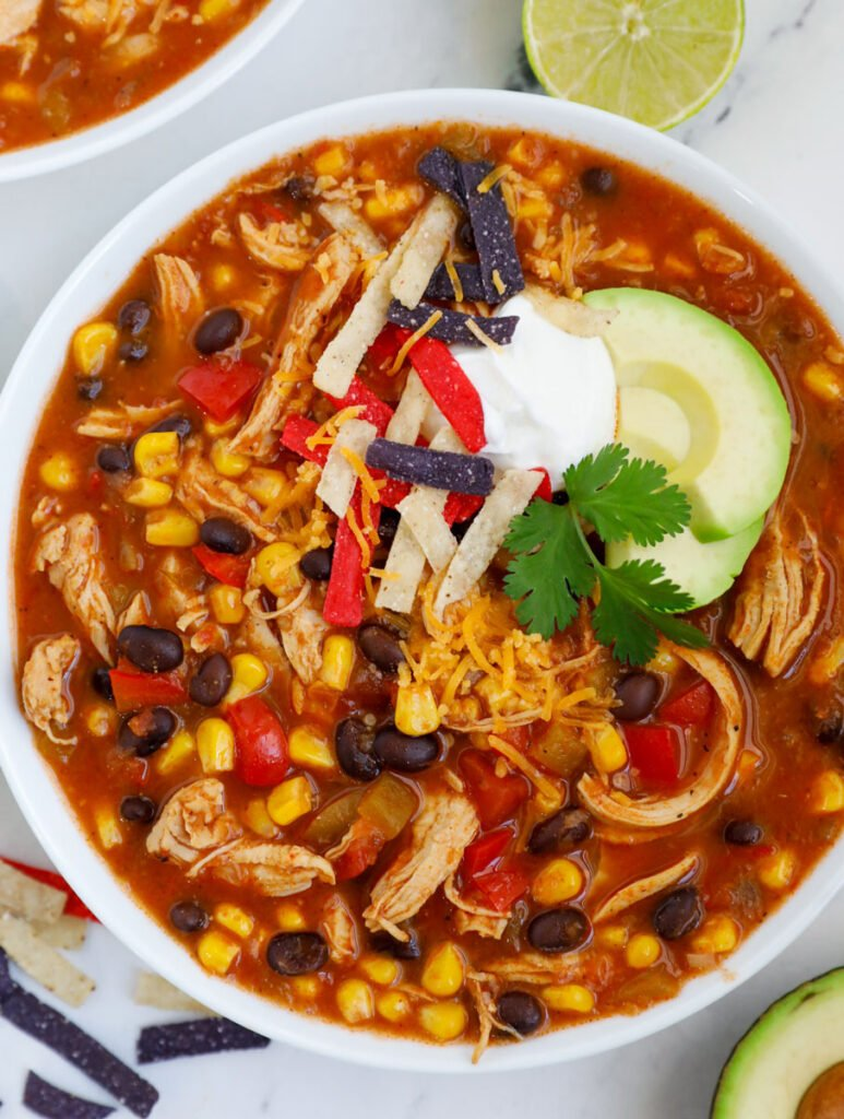 A top down photo of a bowl of chicken enchilada soup.