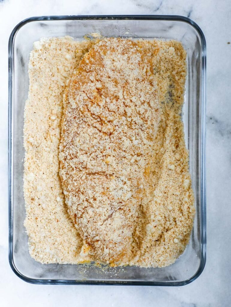Chicken breast in flour with with one side coated.
