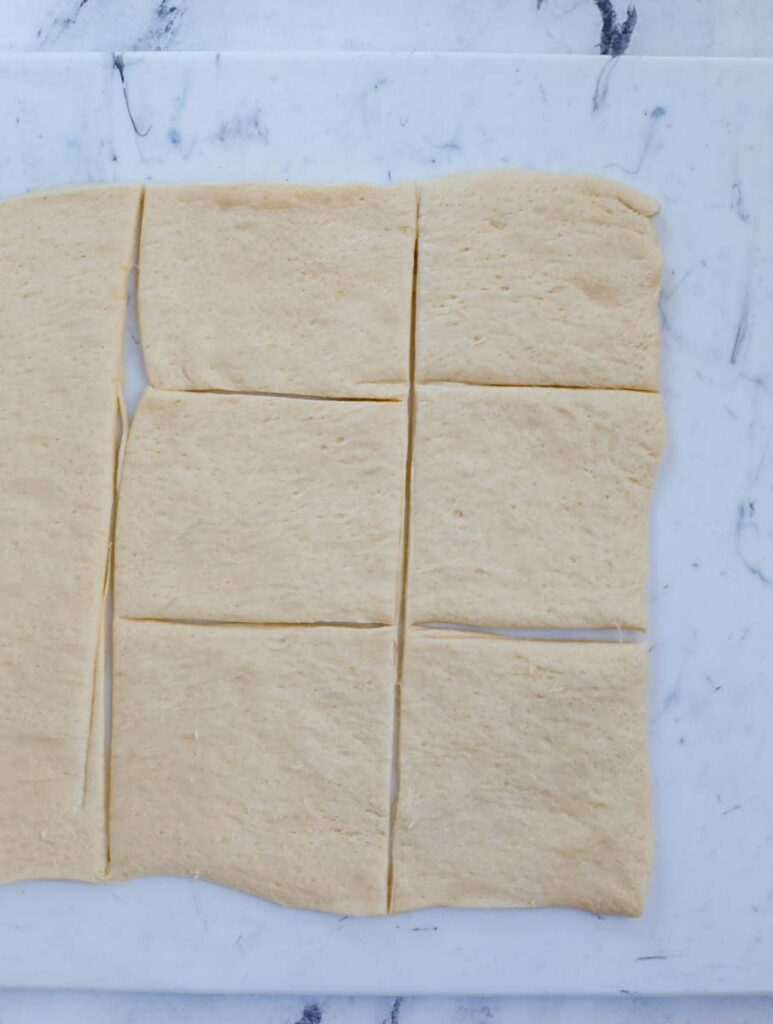 A sheet of puff pastry sliced into squares.