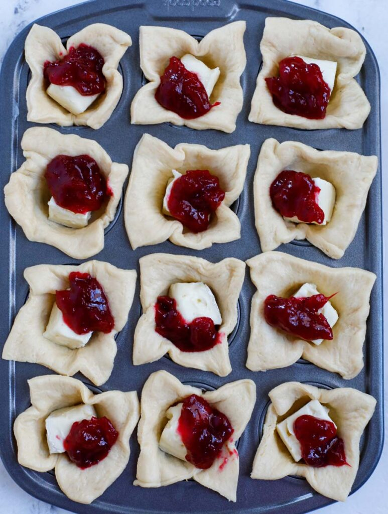 Cranberry sauce on top of brie and puff pastry squares.