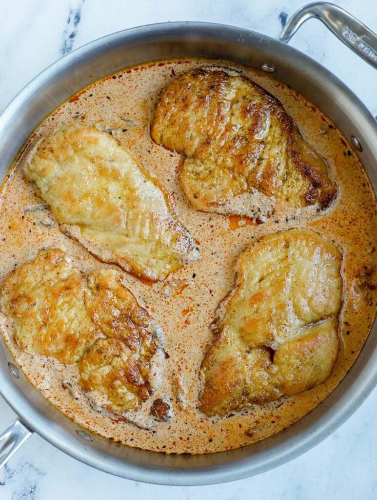 Creamy cajun chicken breasts inside of a skillet.