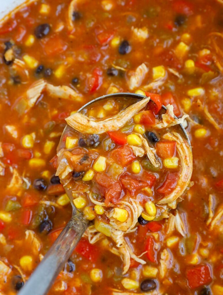 A ladle scooping out enchilada soup.