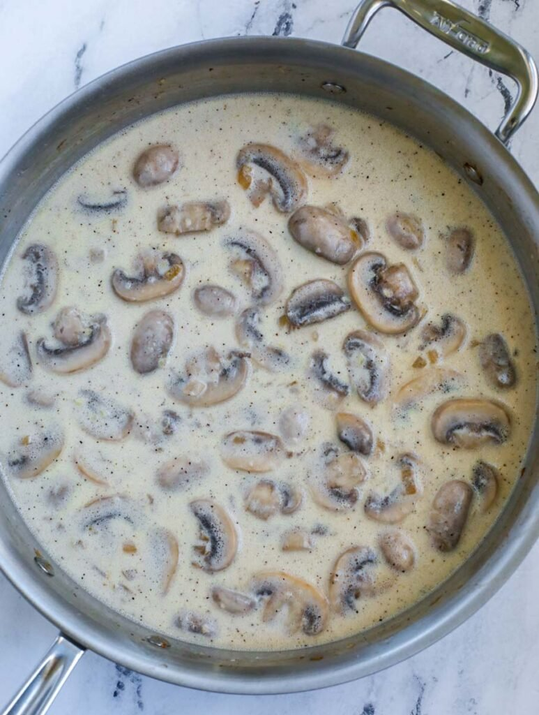 Mushrooms and cream in a pot.