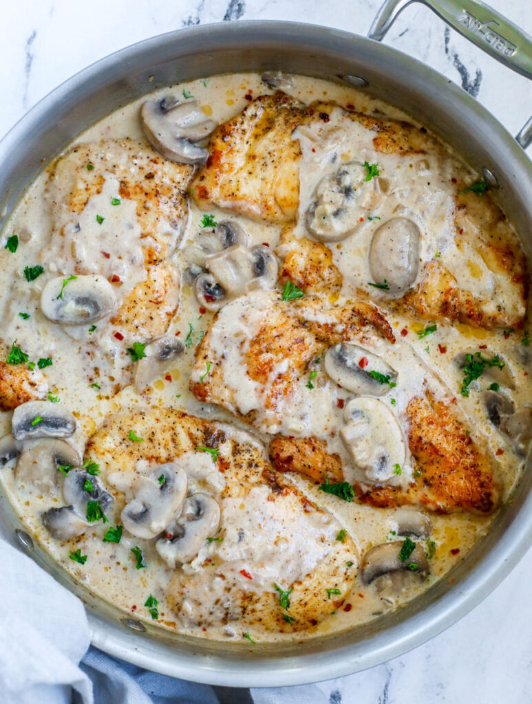 Top down view of creamy mushroom chicken in a silver pot.