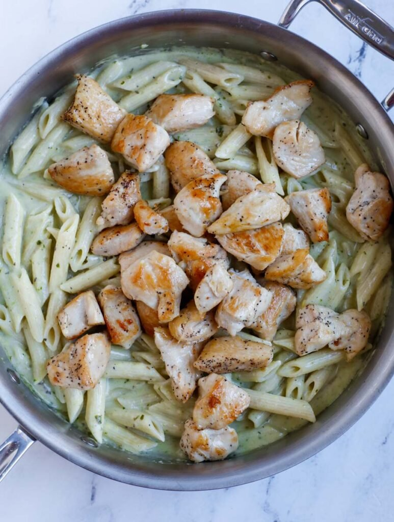 Chicken cubes added into a skillet of pesto covered pasta.