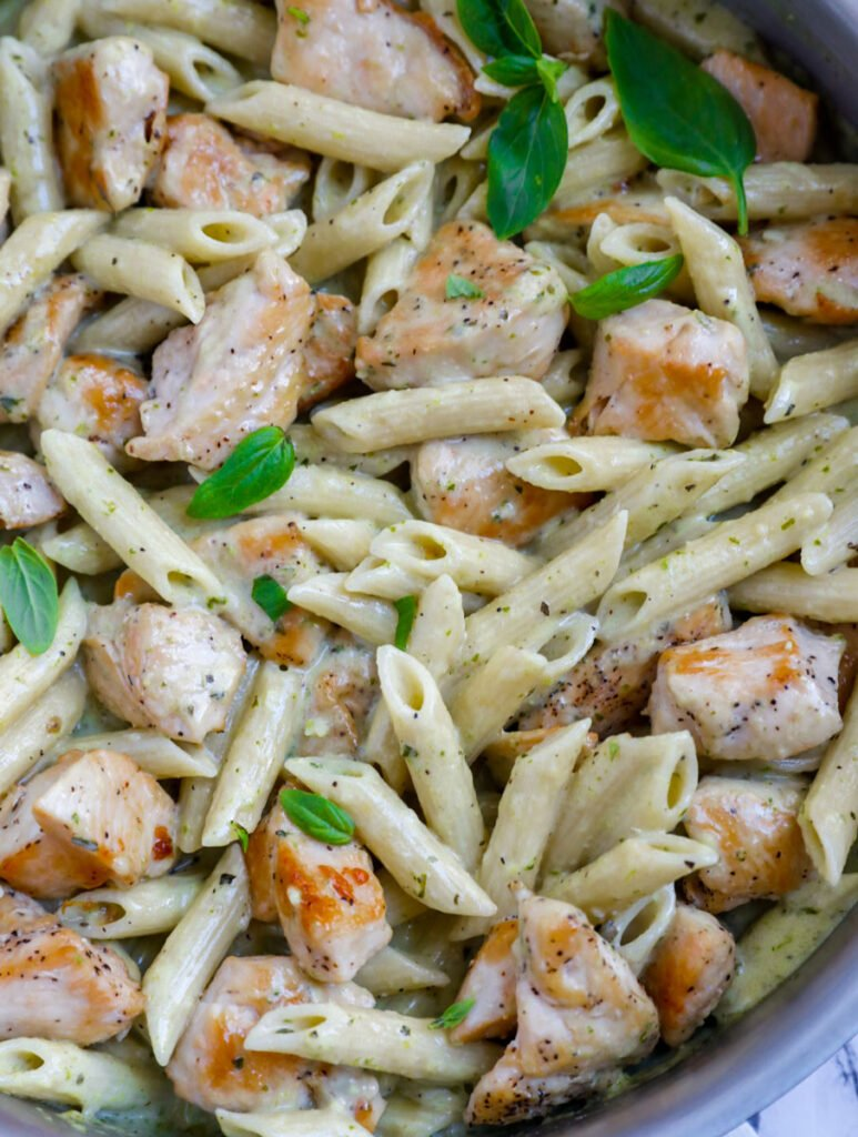 Close up of creamy pesto chicken pasta in a pan.