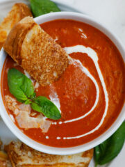 Bowl of tomato soup with bread, basil, and parmesan on top.