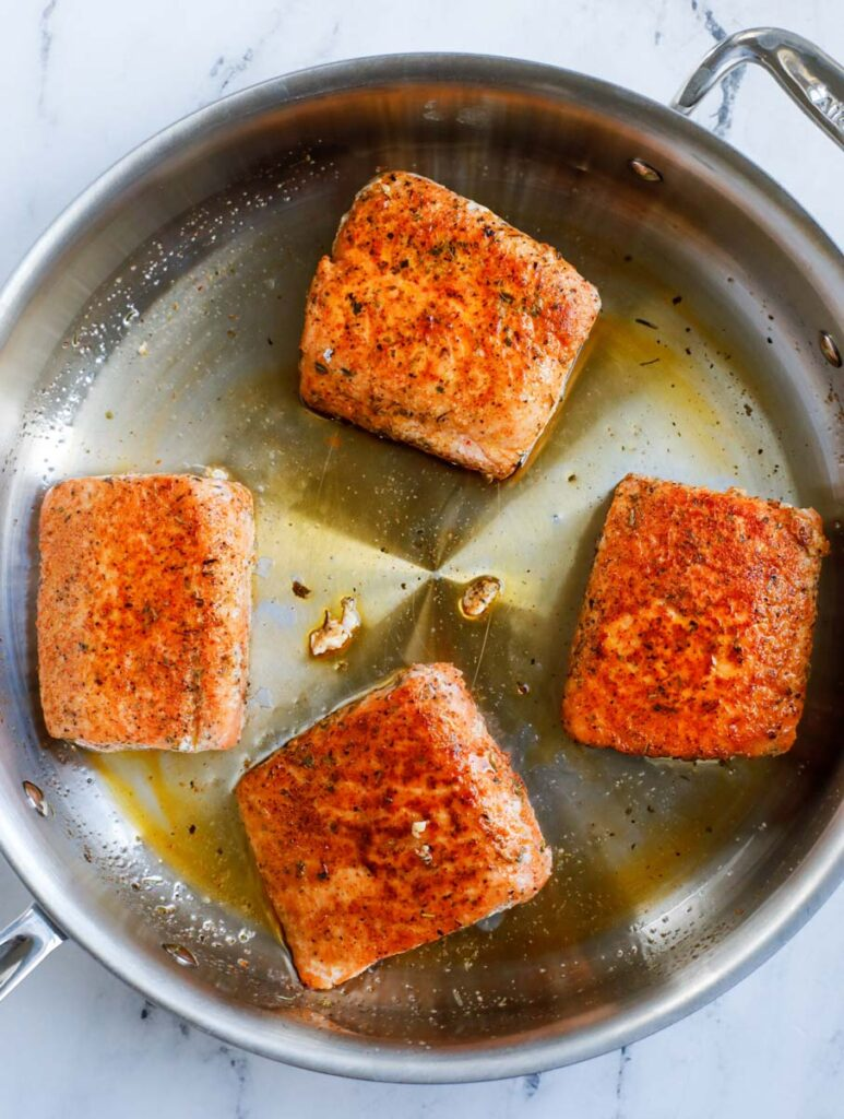 Pan searing the salmon in a pan.