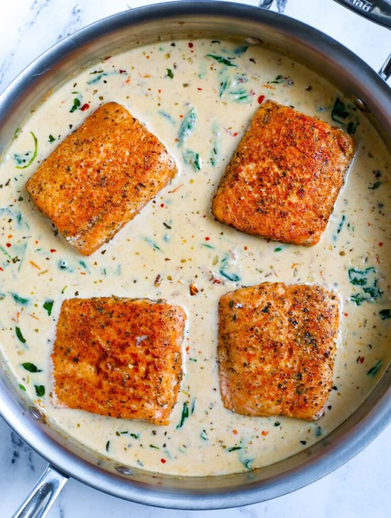 Overhead shot of salmon fillets in cream sauce.