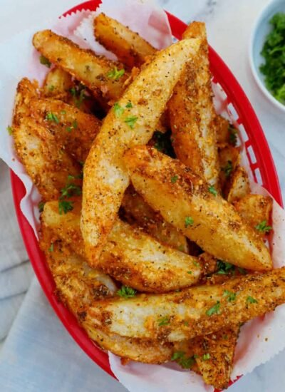 Top down view of crispy potato wedges in a red basket.