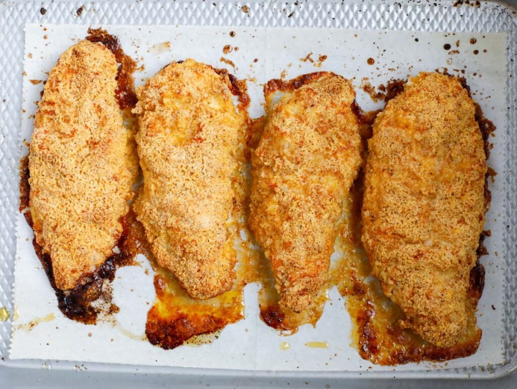 Top down shot of baked chicken breasts on parhcment.