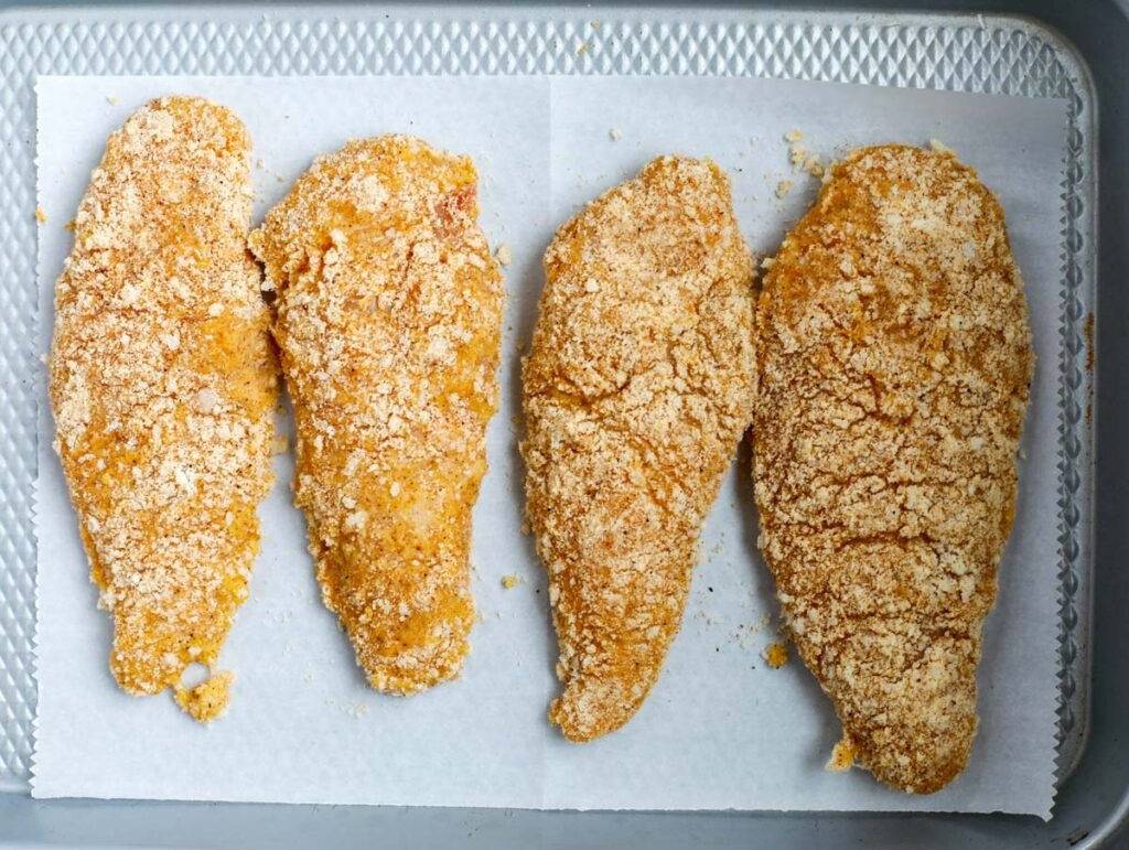 Four chicken breasts coated with almond flour and seasoning on a baking tray/