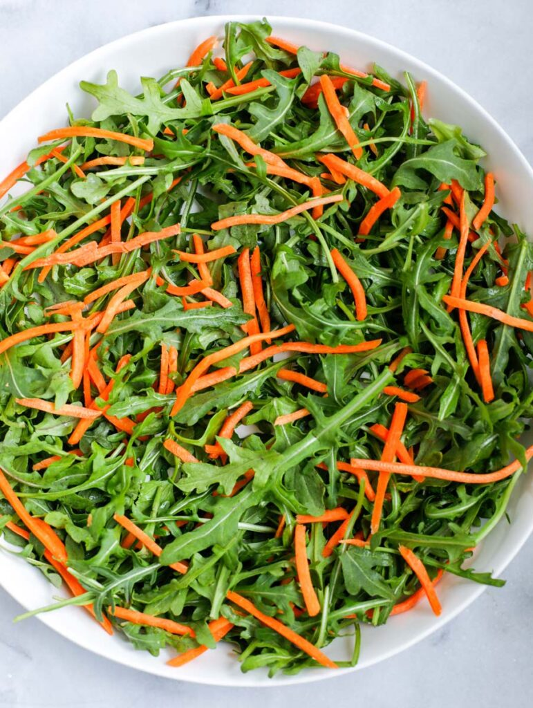 Arugula and shredded carrots in a bowl.